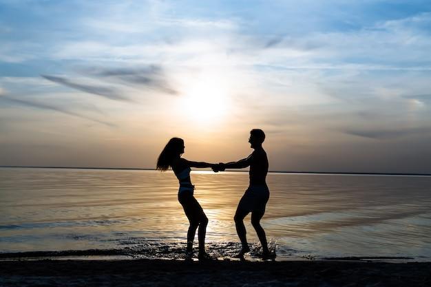 手をつないで水の上で輪になって回転する若いカップル