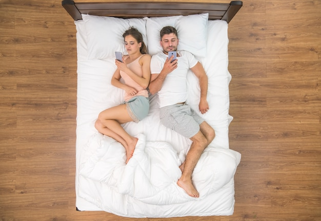 Молодая пара лежала на кровати и разговаривала по телефону. вид сверху