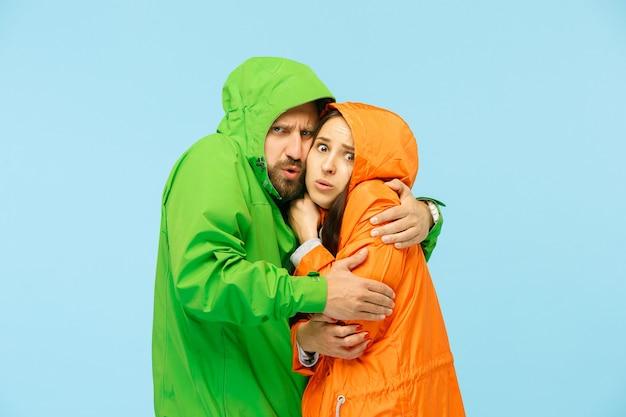 青で隔離の秋のジャケットのスタジオでポーズをとる若いカップル。