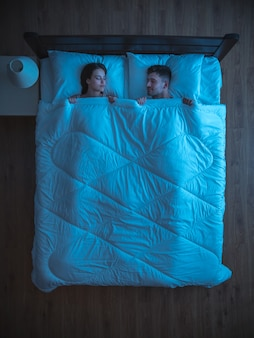 Молодая пара спит на кровати. ночное время. вид сверху