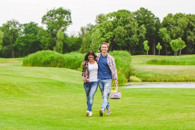 湖の近くを歩いている若いカップル