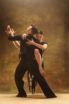 스튜디오 배경에서 관능적인 포즈로 춤추는 금색 드레스를 입은 젊은 댄스 볼룸 커플