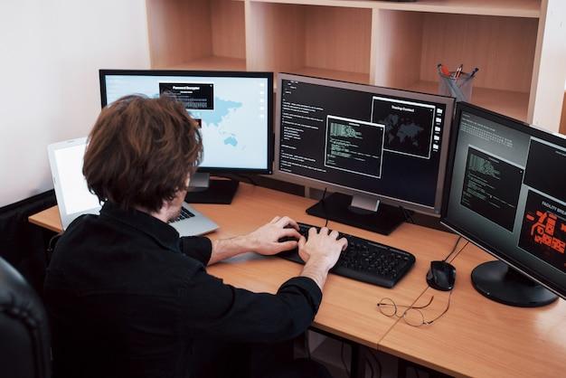 Молодой опасный хакер ломает государственные службы, загружая конфиденциальные данные и активируя вирусы. мужчина использует ноутбук со многими мониторами