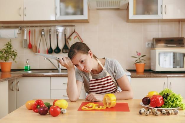 自宅のキッチンで料理をしているエプロンでやせ衰えた若い女性。ダイエットの概念。健康的な生活様式。食べ物を用意します。