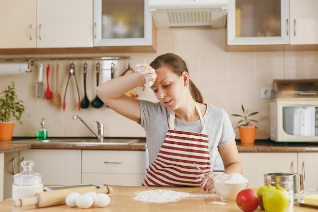 Молодая исхудавшая уставшая женщина сидит за столом с мукой и собирается готовить на кухне пирожные. готовим дома. готовить пищу.