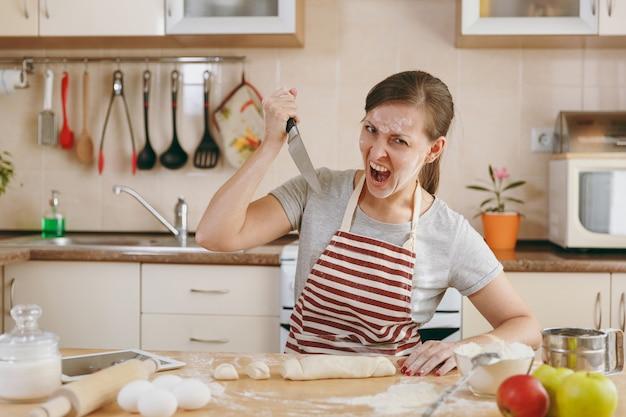 젊은 사악하고 공격적인 여성이 식탁에 앉아 부엌에서 칼로 반죽을 공격합니다. 집에서 요리. 음식을 준비하다.