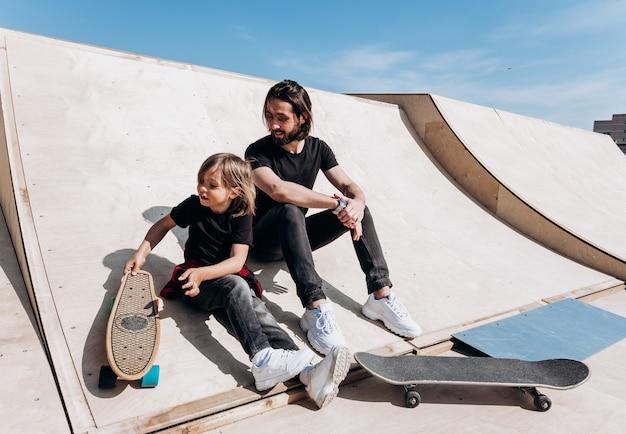 Молодой отец и его сын, одетые в стильную повседневную одежду, сидят вместе на горке рядом со скейтбордами в скейт-парке в солнечный теплый день.