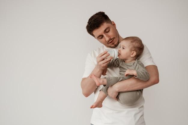 若い父親は子供に注意深く母乳または粉ミルクを与えます。明るい背景の白い部屋で哺乳瓶で授乳し、赤ちゃんを腕に抱きます