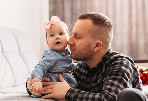 若い父親は、明るい部屋で娘の幼児を優しく見つめます