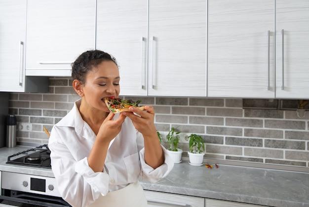 若い女性シェフはチーズなしのビーガンピザを味わいます。