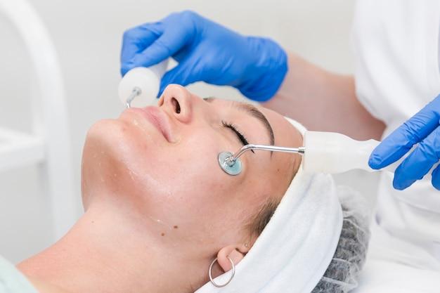 특수 장치 근접 촬영으로 그녀의 얼굴에 미세 전류 절차를 갖는 미용 살롱의 젊은 여성 고객