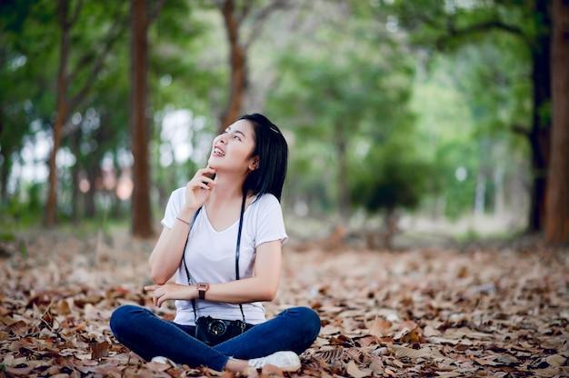 젊은 여성 사진 작가는 사진과 그의 작은 카메라에 만족합니다.