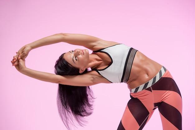 Молодая подтянутая женщина тренируется на розовом студийном фоне