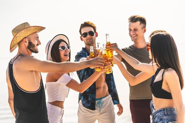 해변 파티에서 맥주와 함께 병을 들고 있는 젊은 친구들