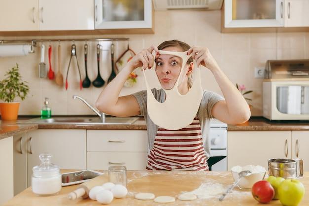 젊고 유쾌하고 웃는 여자는 얼굴에 구멍이 난 반죽을 바르고 부엌에서 즐거운 시간을 보낸다. 집에서 요리. 음식을 준비하다. 무료 사진