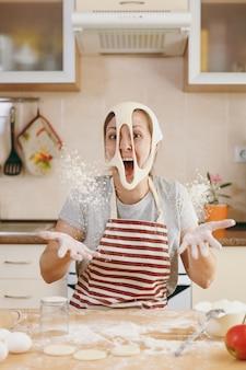 若いおかしい陽気で笑顔の女性は、顔に穴の開いた生地を着て、キッチンで楽しんでいます。クッキングホーム。食べ物を用意します。