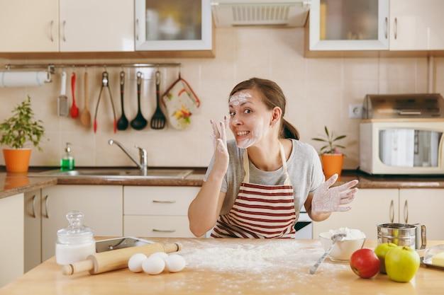 젊고 재미있는 쾌활한 여성이 밀가루로 식탁에 앉아 부엌에서 케이크를 준비하려고 합니다. 집에서 요리. 음식을 준비하다.