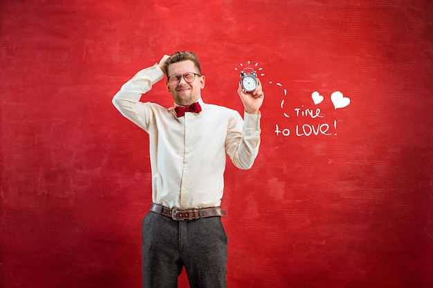 赤いスタジオの背景に抽象的な時計を持つ若い面白い男。コンセプト-おめでとうございます。幸せなバレンタインデーのコンセプト