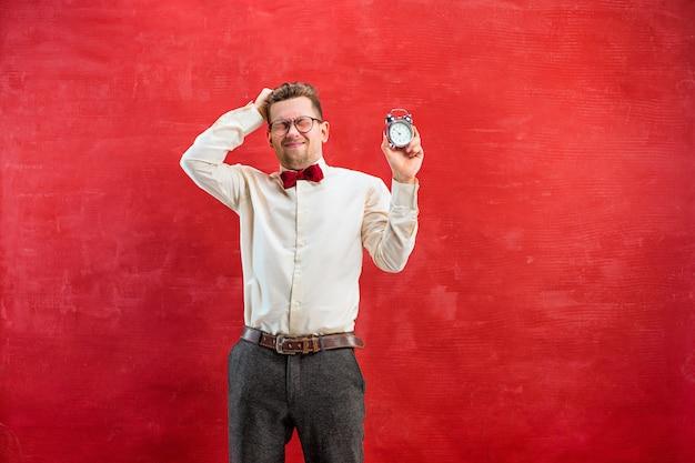 赤いスタジオの背景に抽象的な時計を持つ面白い若者。コンセプト-おめでとう