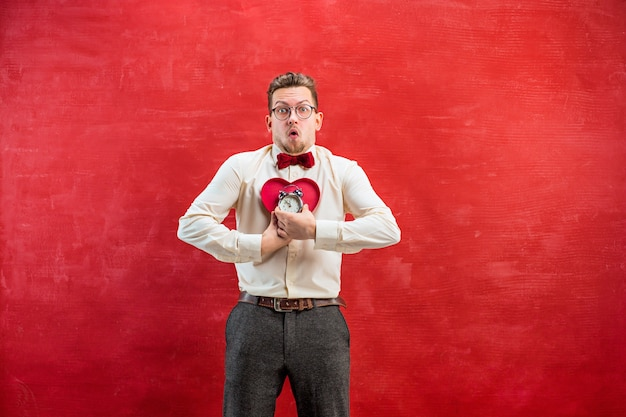 Молодой забавный человек с абстрактным сердцем и часами на красной студии. концепция - время поздравлять