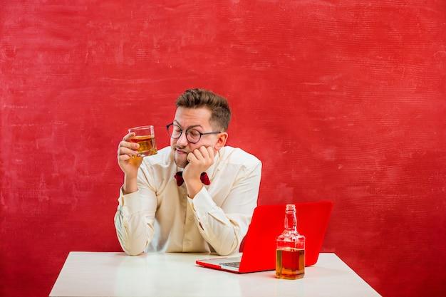 赤いスタジオの背景に聖バレンタインの日にラップトップで座っているコニャックを持つ面白い若者。コンセプト-不幸な愛