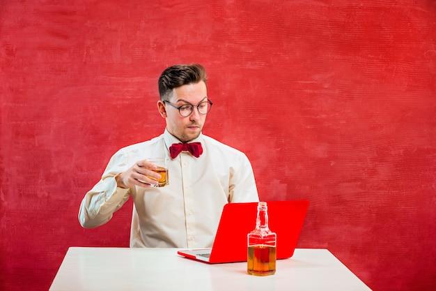赤いスタジオの聖バレンタインの日にラップトップで座っているコニャックを持つ面白い若者。
