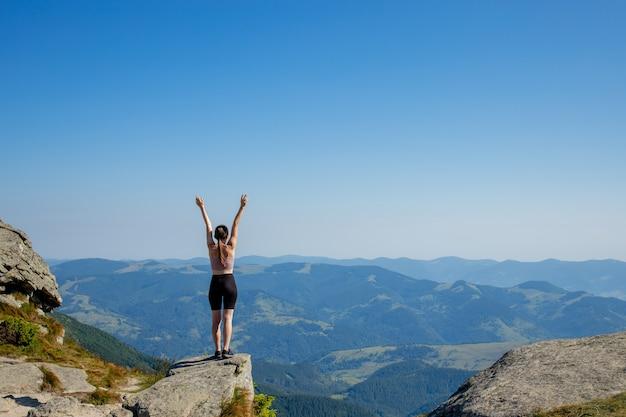 Девушка на вершине горы подняла руки к голубому небу. женщина взошла на вершину и радовалась успеху. вид сзади.