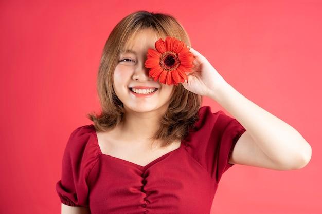 어린 소녀는 한쪽 눈을 덮고있는 붉은 거베라 꽃을 안고