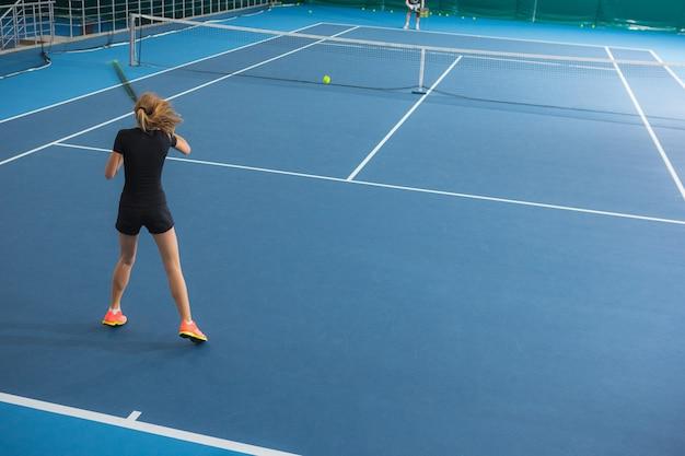 ボールとラケットと閉じたテニスコートの少女