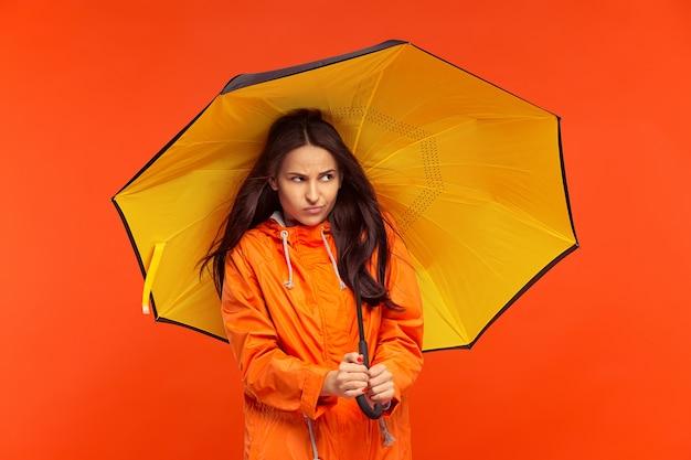 Молодая девушка позирует в студии в осенней куртке, изолированной на красном. человеческие отрицательные эмоции. понятие о холодной погоде. концепции женской моды