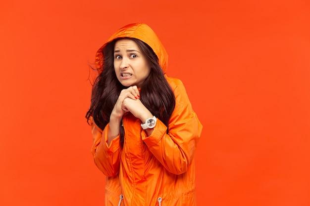 Молодая девушка позирует в студии в осенней куртке, изолированной на красном. человеческие отрицательные эмоции. понятие о холодной погоде