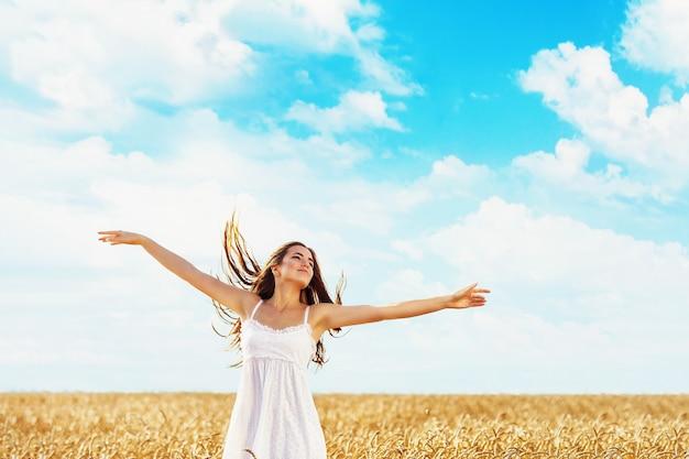 若い女の子は、熟した小麦の畑に向かって日光の光線で手を上げました