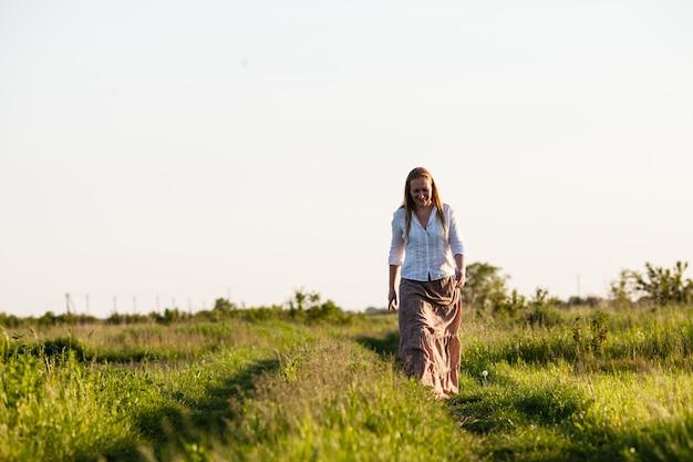 Молодая девушка побежала по полю. концепция легкости и безмятежности, гармонии с природой.