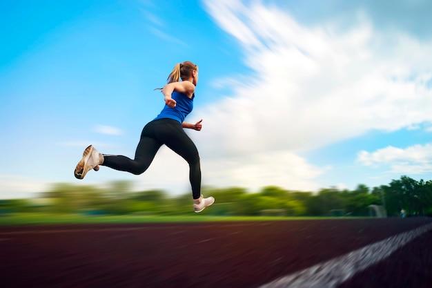 경기장에서 달리는 어린 소녀, 움직이는 데 흐림. 운동 선수가 비행 중에 경기장 점프 사진 주위를 실행합니다. 체육 실기.