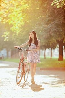 Молодая девушка с велосипедом в парке