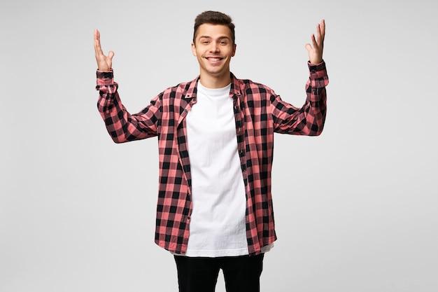 若い男は幸せで陽気で、誰かに会えて喜んでいるかのように腕を上げています