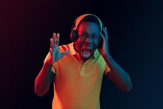 네온 불빛 검은 스튜디오에서 헤드폰으로 젊은 잘 생긴 행복 힙 스터 남자 듣는 음악. 디스코, 나이트 클럽, 힙합 스타일, 긍정적 인 감정, 얼굴 표현, 춤 컨셉