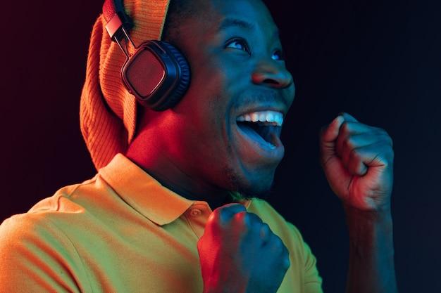 ネオンライト付きの黒いスタジオでヘッドフォンで音楽を聴いている若いハンサムな幸せなヒップスターの男。ディスコ、ナイトクラブ、ヒップホップスタイル、ポジティブな感情、表情、ダンスのコンセプト