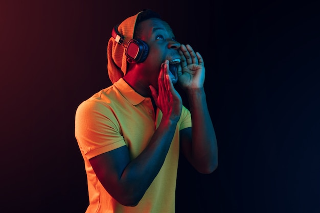 ネオンライトの黒いスタジオでヘッドフォンで音楽を聴いている若いハンサムな幸せなヒップスターの男。ディスコ、ナイトクラブ、ヒップホップスタイル、ポジティブな感情、表情、ダンスのコンセプト