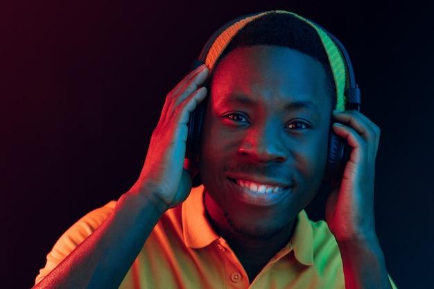 黒のスタジオでヘッドフォンで音楽を聴いている若いハンサムな幸せなヒップスターの男