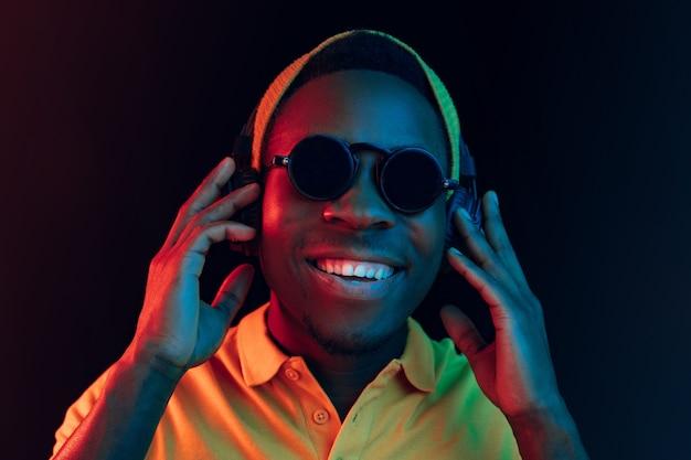 Молодой красивый счастливый хипстерский мужчина слушает музыку в наушниках в черном с неоновыми огнями