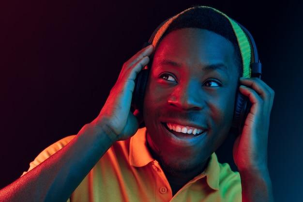 Молодой красивый счастливый хипстерский мужчина слушает музыку в наушниках в черной студии с неоновыми огнями