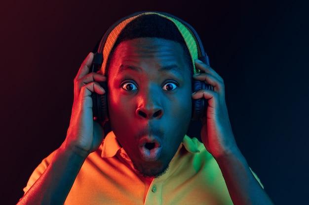 ネオンライト付きの黒いスタジオでヘッドフォンで音楽を聴いている若いハンサムな幸せな驚きのヒップスターの男。ディスコ、ナイトクラブ、ヒップホップスタイル、ポジティブな感情、表情、ダンスのコンセプト