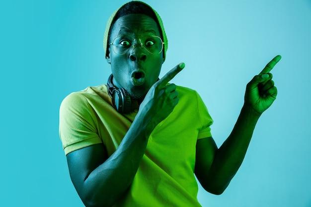 Молодой красивый счастливый удивленный хипстерский человек слушает музыку с наушниками в студии с неоновыми огнями. дискотека, ночной клуб, стиль хип-хоп, положительные эмоции, выражение лица, танцевальная концепция