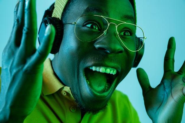 ネオンライトのスタジオでヘッドフォンで音楽を聞いている若いハンサムな幸せな驚きのヒップスターの男。ディスコ、ナイトクラブ、ヒップホップスタイル、ポジティブな感情、表情、ダンスのコンセプト