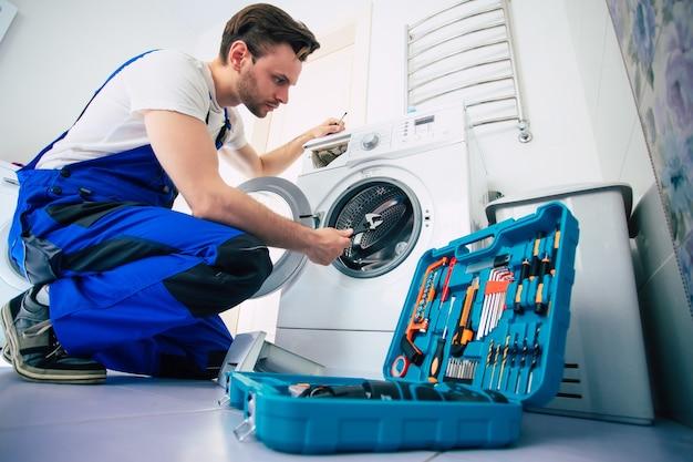 Молодой красавец-ремонтник в костюме рабочего с профессиональным ящиком для инструментов чинит стиральную машину в ванной