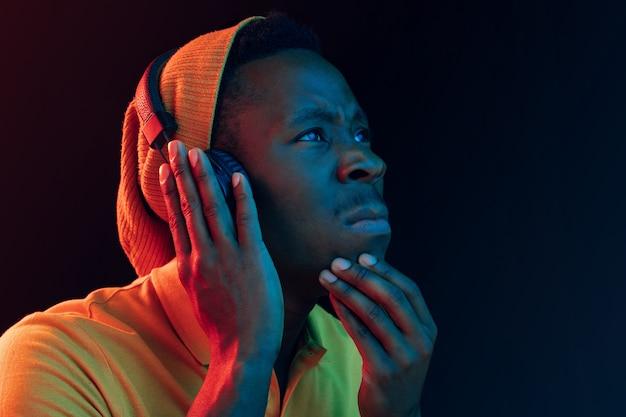Молодой красивый серьезный грустный хипстерский человек слушает музыку в наушниках в черной студии с неоновыми огнями. дискотека, ночной клуб, стиль хип-хоп, положительные эмоции, выражение лица, танцевальная концепция
