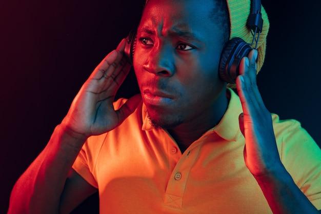 Молодой красивый серьезный грустный хипстерский мужчина слушает музыку в наушниках в черной студии с неоновыми огнями