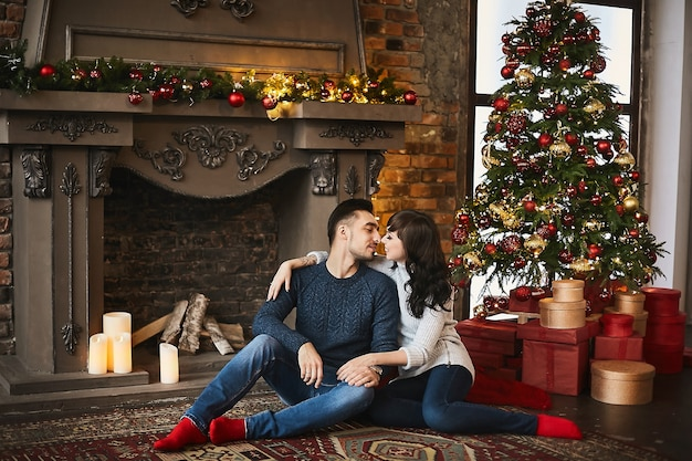 暖かいセーターと赤い靴下を履いて、暖炉とクリスマスツリーの近くの本物のカーペットに抱き合って座っている若い幸せなカップル。クリスマスのお祝いと年末年始。クリスマスムード。