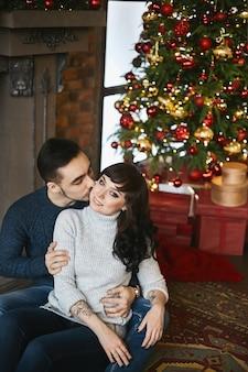 暖かいセーターを着た若い幸せなカップル。暖炉と背景のクリスマスツリーの近くの美しいガールフレンドにキスする若いハンサムな男。クリスマスのお祝いと年末年始。